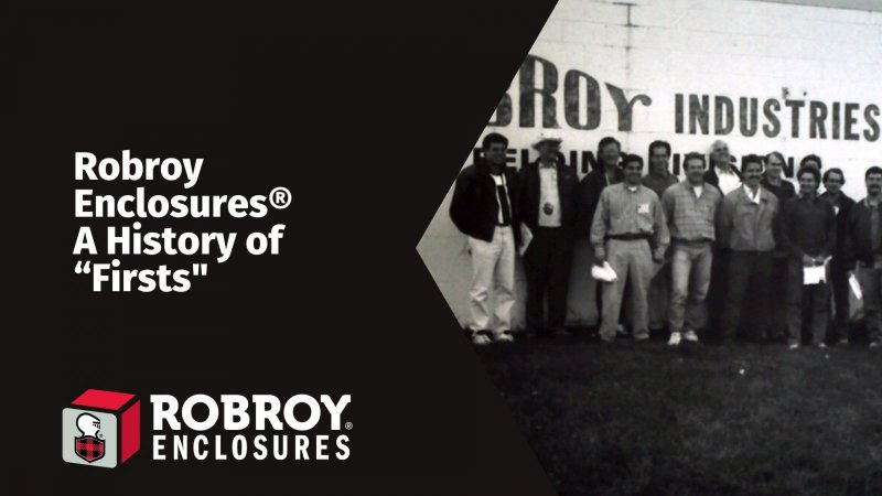 Black and white image of a Group of individuals standing in front of the Robroy Industries logo